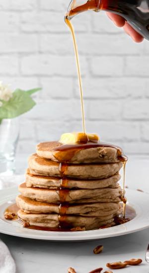 Pouring syrup on Banana-Pecan Pancakes