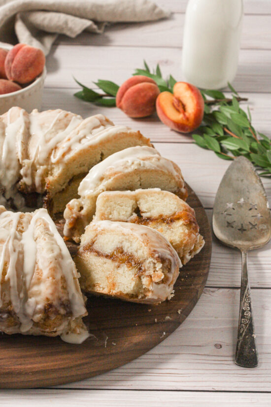Slices of peach pound cake on a cutting board with fresh peaches nearby.