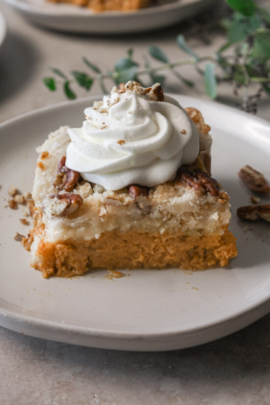 Slice of gluten-free pumpkin pie crisp with dollop of whipped cream on top.