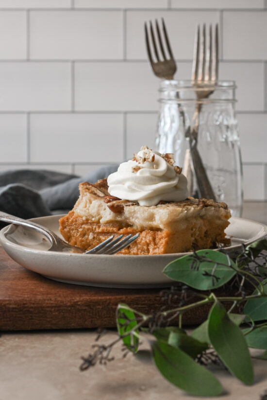 Up close picture of sliced gluten-free pumpkin pie crisp on a plate with greenery next to it.