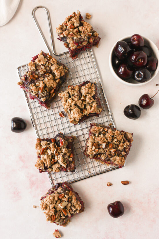 Oatmeal cherry bars on a wire rack with fresh cherries around.