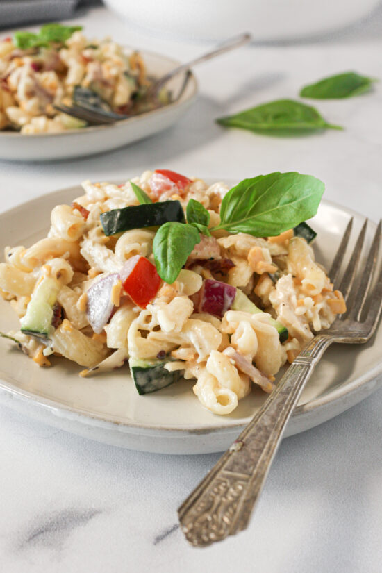 Bacon chicken ranch pasta salad on a small plate with fork.